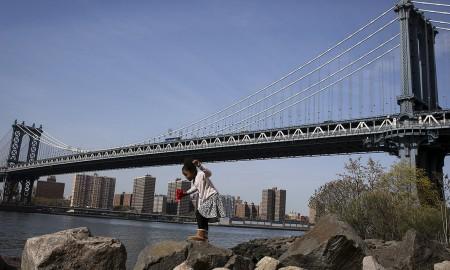 Uma criança brinca nas rochas sob a ponte de Manhattan no bairro de Brooklyn em Nova Iorque, EUA – CARLO ALLEGRI/REUTERS